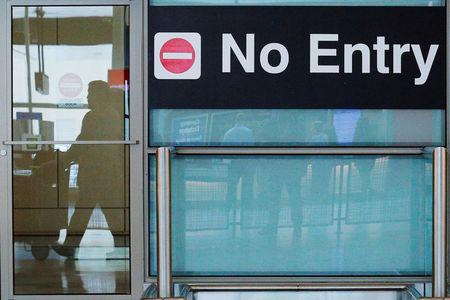 FILE PHOTO: International travelers (reflected in a closed door) arrive on the day that U.S. President Donald Trump's limited travel ban, approved by the U.S. Supreme Court, goes into effect, at Logan Airport in Boston, Massachusetts, U.S., June 29, 2017.   REUTERS/Brian Snyder/File Photo