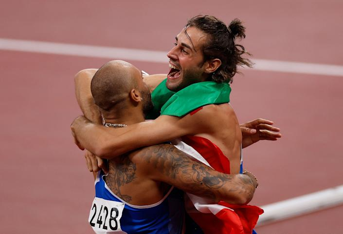 <p>Italy's Lamont Marcell Jacobs celebrates with Italian high jumper Gianmarco Tamberi after winning the men's 100m final during the Tokyo 2020 Olympic Games at the Olympic Stadium in Tokyo on August 1, 2021. (Photo by Odd ANDERSEN / AFP) (Photo by ODD ANDERSEN/AFP via Getty Images)</p>