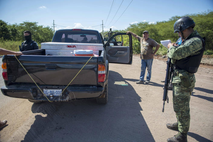 A Mexican soldier mans a checkpoint on the road to the municipality of Novalto, near Culiacan Mexico, Saturday, Oct. 26, 2019. Six 24/7 checkpoints have been set up on the main entrances to the city of Culiacan, to search for weapons or contraband. (AP Photo/Augusto Zurita)
