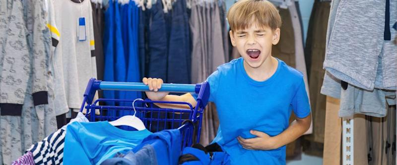 Caucasian boy chooses in shop clothes by new academic year. Is tired, angry and shouts from indignation. Before him the cart loaded with the chosen clothes and footwear