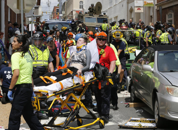 <p>Rescue personnel help injured people after a car ran into a large group of protesters after a white nationalist rally in Charlottesville, Va., Saturday, Aug. 12, 2017. (AP Photo/Steve Helber/AP) </p>