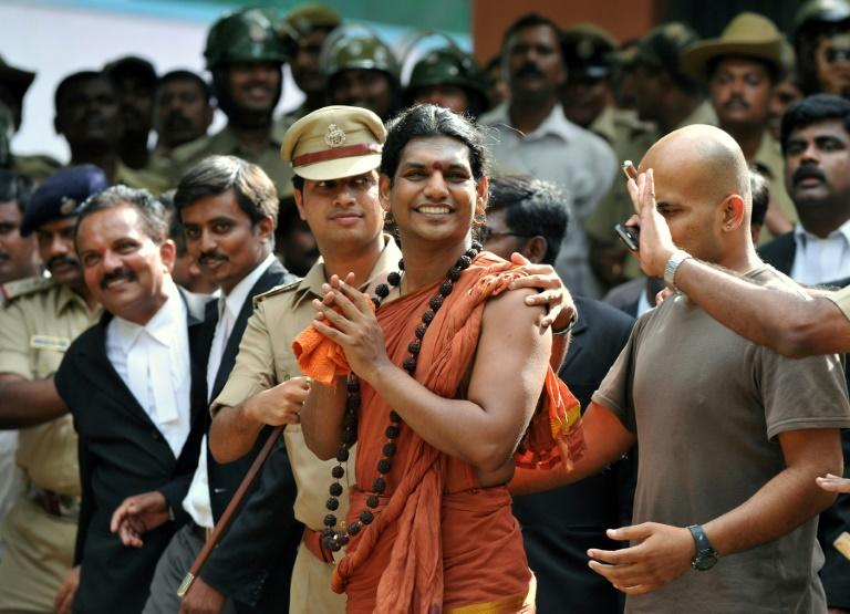 Police escort controversial Hindu Godman Swami Nityananda (center) in 2012 after he appeared at a bail hearing in Ramanagar District, some 50 kilometres from Bangalore, India