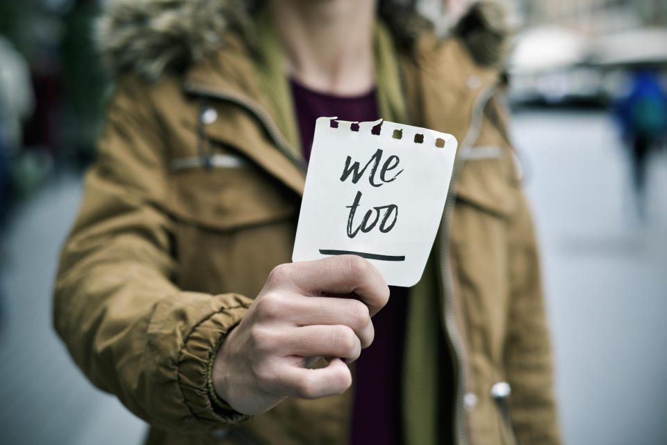 closeup of a young caucasian woman in the street showing a piece of paper with the text me too written in it