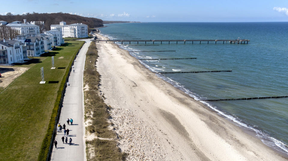 People walk on the beach promenade close to the 'MEDIAN Clinic Heiligendamm' in Heiligendamm, northern Germany, Wednesday, April 14, 2021. The MEDIAN Clinic, specialized on lung diseases, treats COVID-19 long time patients from all over Germany. (AP Photo/Michael Sohn)
