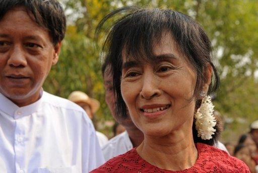 Myanmar opposition leader Aung San Suu Kyi smiles as she leaves after visiting a polling station