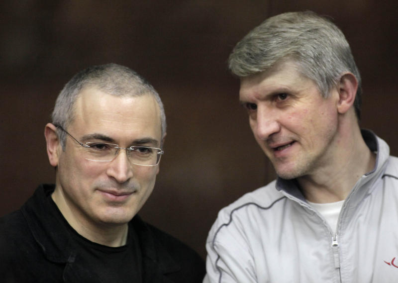 FILE - In this file photo taken on Thursday Dec. 30, 2010, Mikhail Khodorkovsky, left, and his co-defendant Platon Lebedev talk behind a glass enclosure at a court room in Moscow, Russia. The European Court of Human Rights on Thursday, July 25, 2013, has dismissed claims that Russian tycoon Mikhail Khodorkovsky was prosecuted for political reasons. But the court said Thursday that Russia unfairly charged him huge tax arrears, and that Russian authorities unfairly sent him and business partner Platon Lebedev to far-away penal colonies. (AP Photo/Alexander Zemlianichenko Jr, File)