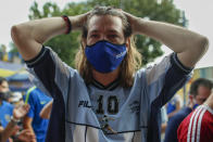 A fan mourns the death of Diego Maradona at the entrance of the Boca Juniors stadium, known as La Bombomera, in Buenos Aires, Argentina, Wednesday, Nov. 25, 2020. The Argentine soccer great who was among the best players ever and who led his country to the 1986 World Cup title before later struggling with cocaine use and obesity, died from a heart attack on Wednesday at his home in Buenos Aires. He was 60. (AP Photo/Natacha Pisarenko)