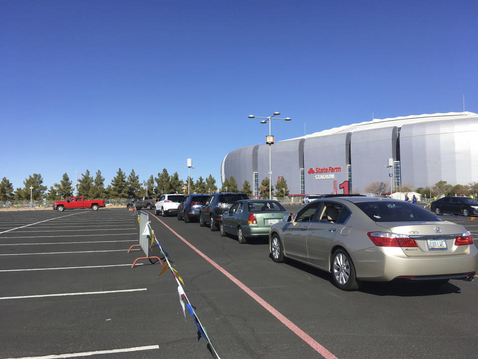 Drivers wait in line to get the COVID-19 vaccine in the parking lot of the State Farm Stadium in Glendale, Ariz., on Monday, Jan. 11, 2021. The Arizona Cardinals' stadium opened as a vaccination site Monday that will be a 24-7 operation. (AP Photo/Terry Tang)