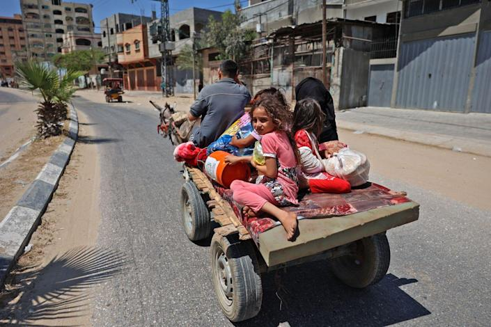 A Palestinian family flees on a cart pulled by a donkey.