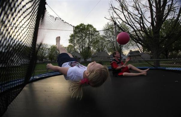 Parker Roos, who suffers from Fragile X, plays on a trampoline with his sister Allison in his backyard at his home in Canton, Illinois, April 4, 2012. Both of Holly Roos' children have Fragile X. Parker is an energetic and expressive 12 year old; and Allison, though possessing the same amount of youthful playfulness, displays much milder symptoms than her older brother.