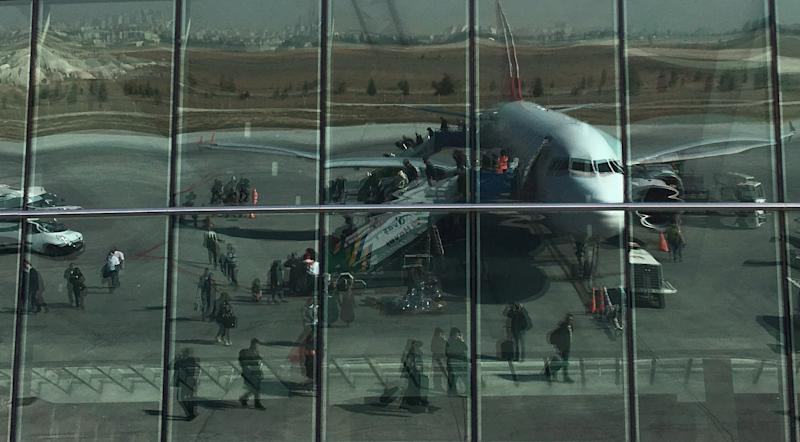Passengers are reflected in the glass of the departure hall as they leave from a Turkish Airlines aircraft at the airport in Konya