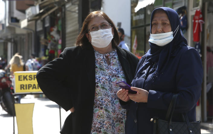 Two women look on as people march in silence to honor the victims in the burned out makeshift hospital in North Macedonia's northwestern town of Tetovo, Saturday, Sept. 11, 2021. Hundreds of people have marched Saturday in northwestern town of Tetovo to honor their 14 countrymen killed in a deadly fire that broke earlier this week and destroyed COVID-19 field hospital. (AP Photo/Boris Grdanoski)