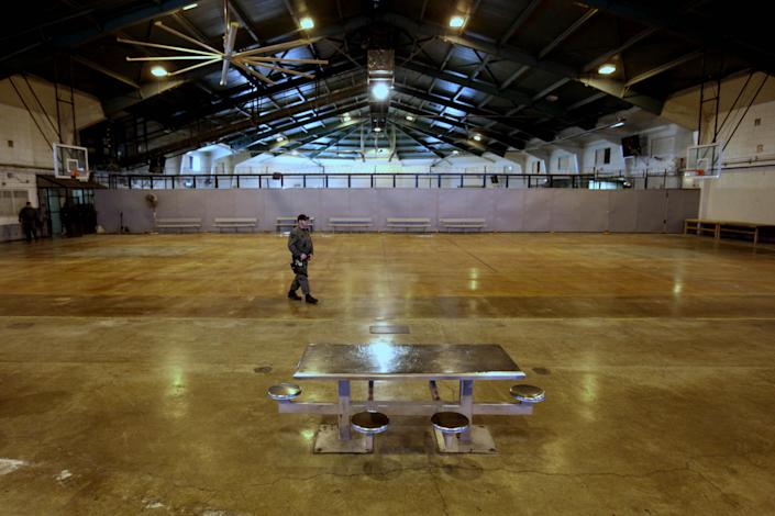 FILE - In this March 2, 2012 file photo, a correctional officer walks through a gymnasium that once held nearly 700 inmate bunks at the Deuel Vocational Institution in Tracy, Calif. Crowding in state prisons has been reduced under a two-year-old state law, backed by Gov. Jerry Brown, that is sending less serious offenders to county jails instead of state prisons. Gov. Jerry Brown faces a midnight deadline of May 2, to say how the state will further reduce its inmate population.(AP Photo/Rich Pedroncelli, File)