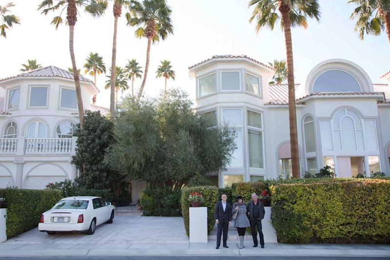 From left, Craig Tann, Laura and Jack Sommer stand in front of the Sommers' home in Las Vegas's Spanish Trail neighborhood on Thursday, Dec. 12, 2013. Jack Sommer, a casino owner-turned-commercial developer, is asking $7.85 million to sell the home, and he's willing to accept the online currency bitcoin for the deal. (AP Photo/Las Vegas Review-Journal, Alex Federowicz)
