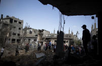 Palestinians inspect their destroyed houses following overnight Israeli airstrikes in the town of Beit Hanoun, northern Gaza Strip, Friday, May 14, 2021. (AP Photo/Khalil Hamra)