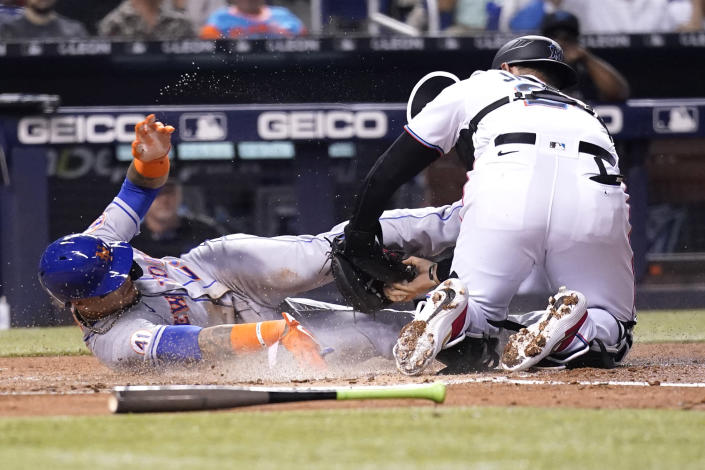 New York Mets' Javier Baez, left, scores past Miami Marlins catcher Alex Jackson, right, during the first inning of a baseball game, Wednesday, Aug. 4, 2021, in Miami. (AP Photo/Lynne Sladky)
