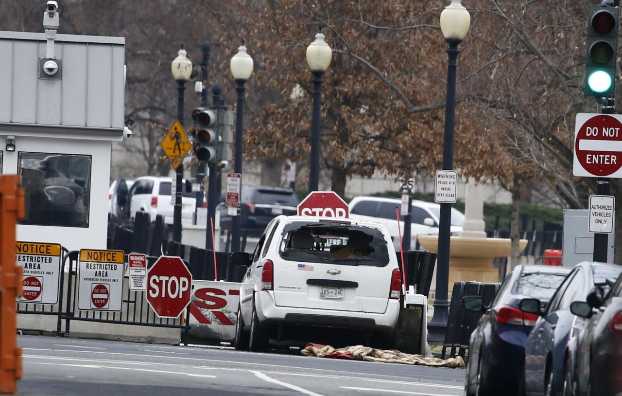 A passenger vehicle that struck a security barrier sits near the White House in Washington, U.S.,  February 23, 2018. REUTERS/Jim Bourg