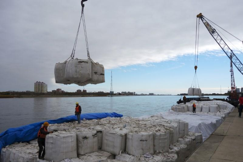 Workers stand near a crane unloading sacks of imported soybeans from Russia at Heihe port in Heilongjiang