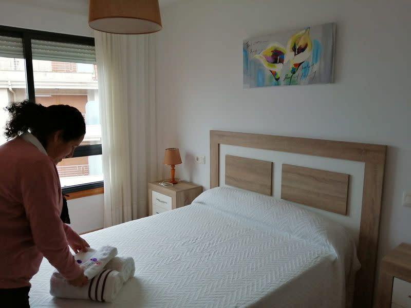 Airbnb host Perla Requejo folds towels in the property that she rents to holidaymakers on Airbnb in Sanxenxo