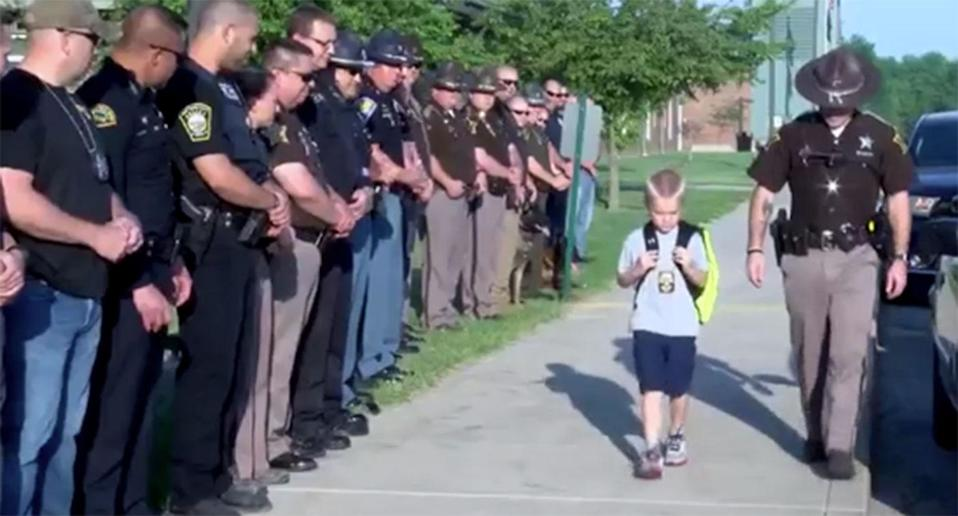 Dakota Pitts, the five-year-old son of Indiana police officer Rob Pitts, who was shot and killed by a homicide suspect, receives a guard of honour on his first day back to school following the tragedy. Source: WTHI-TV