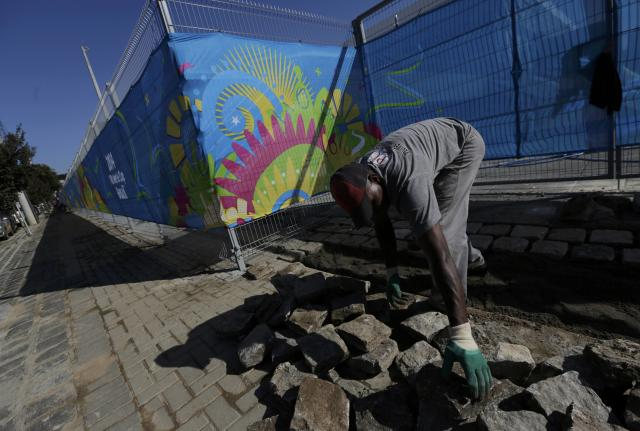 A construction worker continues the installation of paving stones outside the Arena Baixada soccer stadium in Curitiba, June 13, 2014. The stadium will host the first of four 2014 World Cup matches on June 16. REUTERS/Henry Romero (BRAZIL - Tags: BUSINESS CONSTRUCTION SOCCER SPORT WORLD CUP)