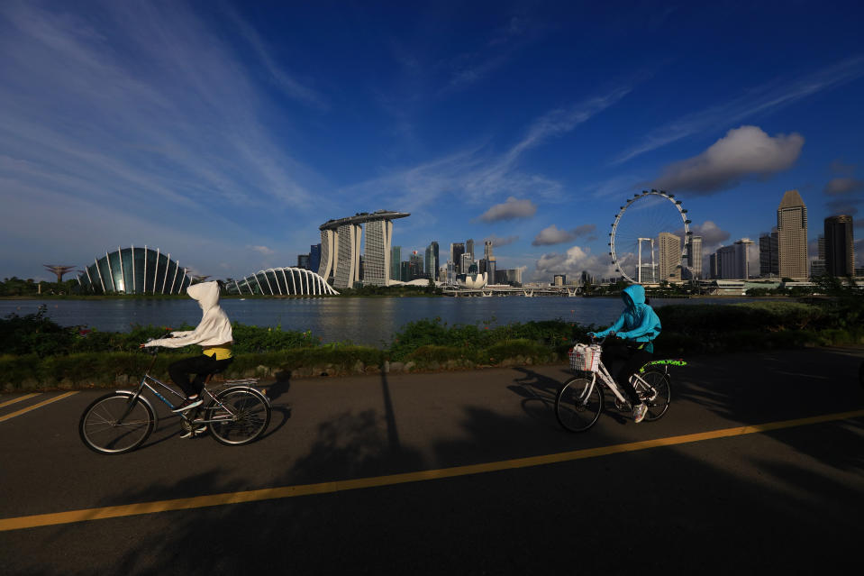 People cycle along the bayfront with the city skyline seen in the background on June 3, 2021 in Singapore. Singapore enters a month long heightened alert from May 16 to June 13 to curb the spread of COVID-19 cases in the local community. New restrictions on movements and activities have been introduced such as limiting social interaction to two, prohibiting dining out and a reduced operating capacity at shopping malls, offices and attractions. (Photo by Suhaimi Abdullah/NurPhoto via Getty Images)
