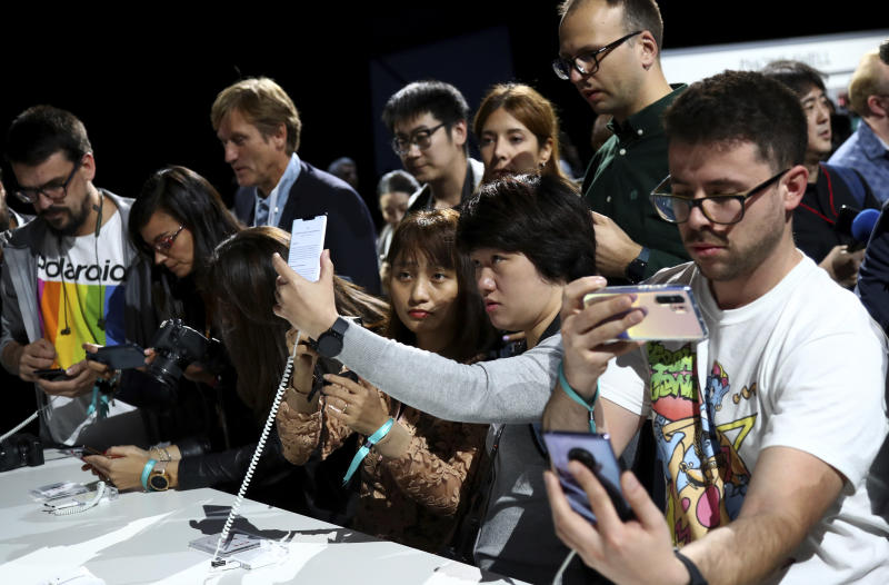 Visitors take pictures of new devices of China's smartphone manufacturer Huawei during an event in Munich, Germany, Thursday, Sept. 19, 2019. (AP Photo/Matthias Schrader)