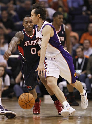 Phoenix Suns' Steve Nash, ront right, looks to pass as Atlanta Hawks' Jeff Teague (0) defends during the first half of an NBA basketball game on Wednesday, Feb. 15, 2012, in Phoenix. (AP Photo/Matt York)