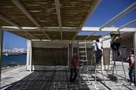 Workers install a bamboo screen at a bar restaurant in Chora, on the Aegean island of Naxos, Greece, Tuesday, May 11, 2021. Greece Friday became the latest country to open up its vacation season as it dismantles lockdown restrictions and focuses its vaccination program on the islands. (AP Photo/Thanassis Stavrakis)