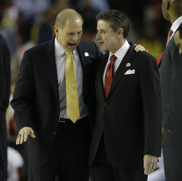 Michigan head coach John Beilein, left, speaks with Louisville head coach Rick Pitino before the first half of the NCAA Final Four tournament college basketball championship game Monday, April 8, 2013, in Atlanta. (AP Photo/Charlie Neibergall)