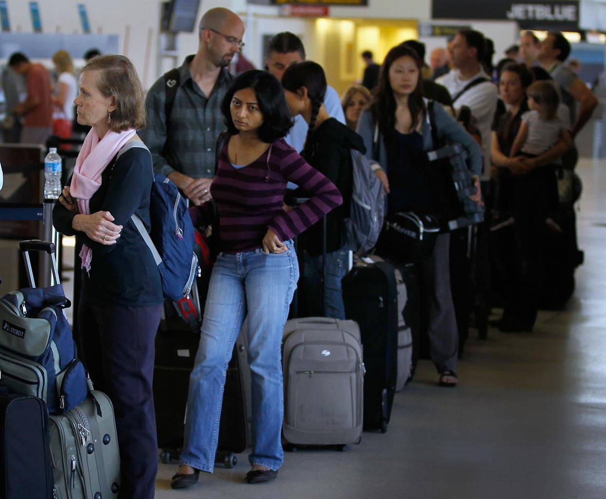 Airline travellers stand in line to get to the United airlines ticketing counter at Newark Airport in Newark, New Jersey on Aug. 29, 2011.