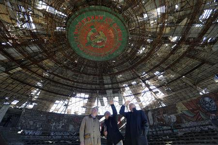Laurent Levi-Strauss and Graham Bell, experts at heritage organisation Europa Nostra and Mario Aymerich, technical consultant of the European Investment Bank Institute stand inside Buzludzha Monument, Stara Planina mountain, September 27, 2018.  REUTERS/Stoyan Nenov