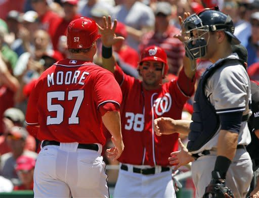 Washington Nationals Tyler Moore (57) is greeted at home by Michael Morse (38) after they both scored on a double by Jesus Flores, as New York Yankees catcher Russell Martin,right, looks on during the second inning of a baseball game at Nationals Park on Saturday, June 16, 2012 in Washington. (AP Photo/Alex Brandon)