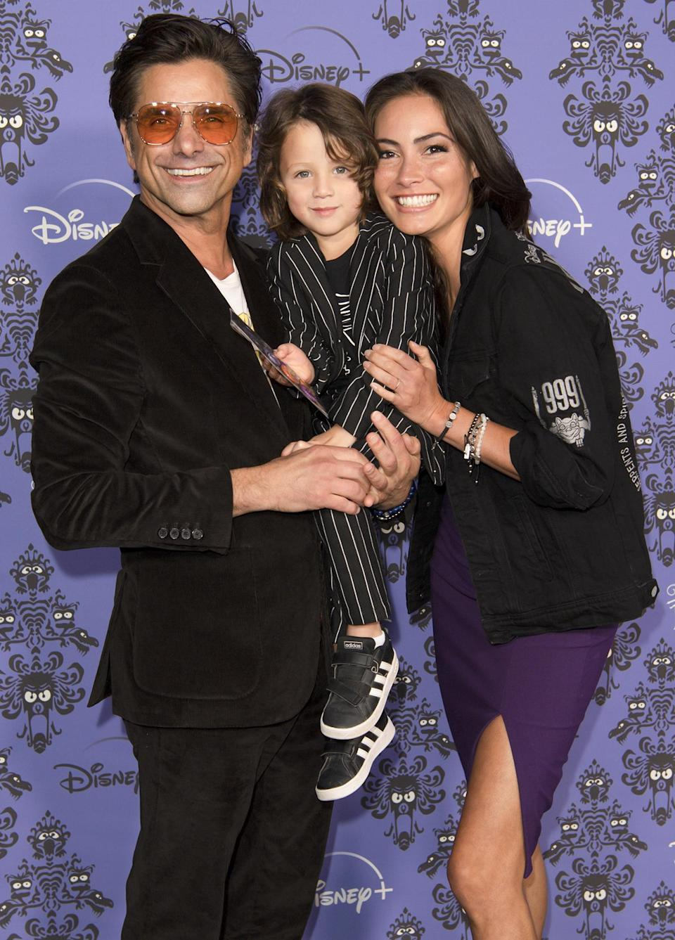 <p>John Stamos, wife Caitlin and their son Billy stick together on Oct. 7 at the Los Angeles premiere of <em>Muppets Haunted Mansion. </em></p>