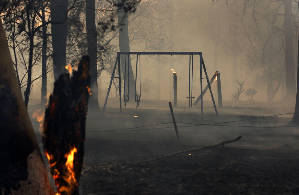 Pictured is a charred swing among burnt trees. Source: AAP