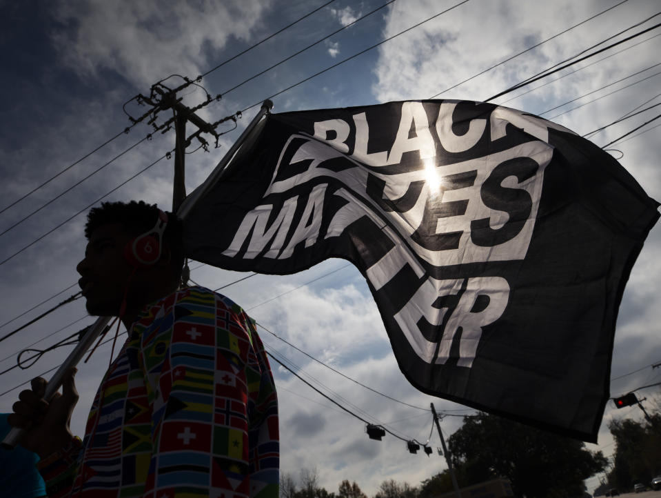 FILE - In this Dec. 12, 2020, file photo, MD Crawford carries a Black Lives Matter flag before a march in La Marque, Texas to protest the shooting of Joshua Feast, 22, by a La Marque police officer. A financial snapshot shared exclusively with The Associated Press shows the Black Lives Matter Global Network Foundation took in just over $90 million last year. (Stuart Villanueva /The Galveston County Daily News via AP, File)
