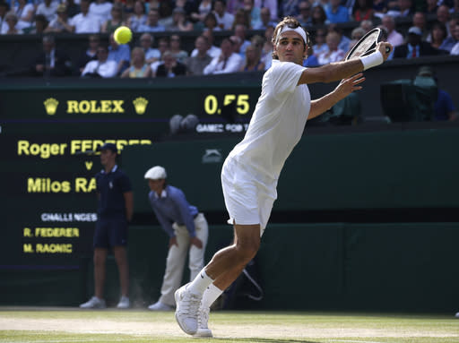 Roger Federer of Switzerland reaches out to play a return to Milos Raonic of Canada during their men's singles semifinal match at the All England Lawn Tennis Championships in Wimbledon, London, Friday, July 4, 2014. (AP Photo/Pavel Golovkin)