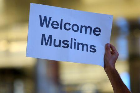 "Retired engineer John Wider, 59, holds up a sign reading ""Welcome Muslims"" as international travelers arrive at Los Angeles International Airport in Los Angeles, California, U.S., June 29, 2017.  REUTERS/Mike Blake"