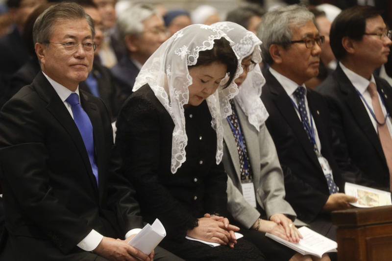 South Korean President Moon Jae-in and his wife Kim Jung-sook, second from left, sit inside St. Peter's Basilica for a Mass for Peace celebrated by Vatican Secretary of State Pietro Parolin at the Vatican, Wednesday, Oct. 17, 2018. South Korea's president is in Italy for a series of meetings that will culminate with an audience with Pope Francis at which he's expected to extend an invitation from North Korean leader Kim Jong Un to visit. (AP Photo/Gregorio Borgia)