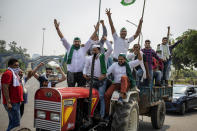 Indian farmers shout slogans as they ride tractors towards New Delhi in Noida, India, Friday, Sept. 25, 2020. Hundreds of Indian farmers took to the streets on Friday protesting new laws that the government says will boost growth in the farming sector through private investments, but they fear these are likely to be exploited by private players for buying their crops cheaply. (AP Photo/Altaf Qadri)