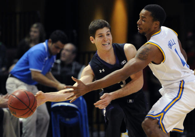 Northwestern's Dave Sobolewski, left, passes the ball around UCLA's Norman Powell during the first half of an NCAA college basketball game at the Las Vegas Invitational on Friday, Nov. 29, 2013, in Las Vegas. (AP Photo/David Becker)