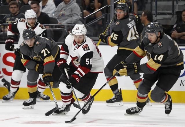 Vegas Golden Knights' Nicolas Hague, right, battles for the puck with Arizona Coyotes' Michael Bunting during the first period of an NHL hockey game Sunday, Sept. 16, 2018, in Las Vegas. (AP Photo/John Locher)