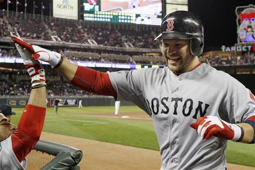 Boston Red Sox' Cody Ross celebrates his two-run, game-tying home run off Minnesota Twins pitcher Jason Marquis in the seventh inning of a baseball game Monday, April 23, 2012, in Minneapolis. (AP Photo/Jim Mone)