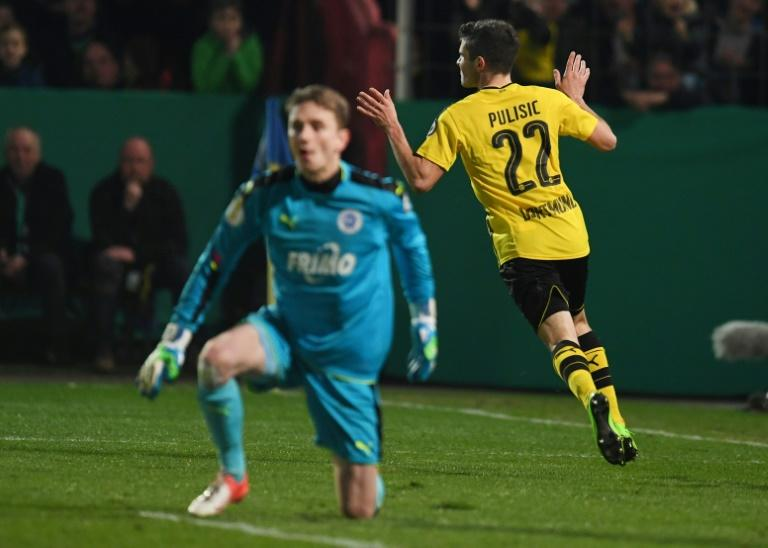 Dortmund's midfielder Christian Pulisic (R) celebrates scoring the opening goal during the German Cup DFB Pokal quarter-final football match Sportfreunde Lotte v BVB Borussia Dortmund, in Osnabruck, northern Germany on March 14, 2017