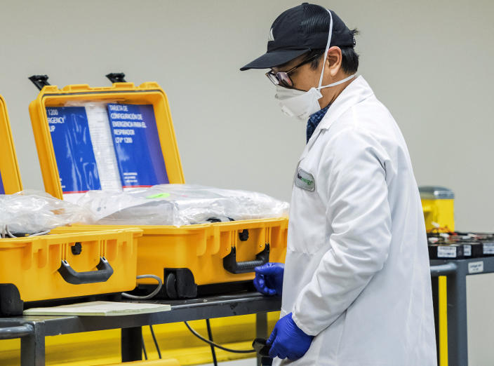 In this Saturday, March 28, 2020, file photo, a staffer works on a ventilator refurbishing assembly line at Bloom Energy in Sunnyvale, Calif. The COVID-19 outbreak has prompted companies large and small to rethink how they do business. Bloom Energy makes hydrogen fuel cells. But recently, they have been refurbishing old ventilators so hospitals can use them to keep coronavirus patients alive. (Beth LaBerge/KQED via AP, Pool, File)