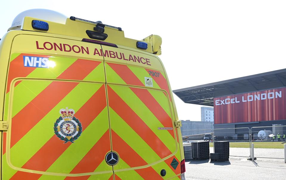 London Ambulance Service vehicles are seen outside the ExCeL London exhibition centre in London on March 27, 2020, that is being transformed into a field hospital to be known as the NHS Nightingale Hospital to help with the coronavirus outbreak. - Britain on March 24 said it will open a 4,000-bed field hospital at a London exhibition centre to treat coronavirus cases in the latest measure to tackle the outbreak after the government ordered a nationwide lockdown. The British health secretary told a news conference the temporary hospital, to be known as the NHS Nightingale Hospital, would open at the ExCeL centre in east London with two wards each with a capacity for 2,000 people. (Photo by Glyn KIRK / AFP) (Photo by GLYN KIRK/AFP via Getty Images)