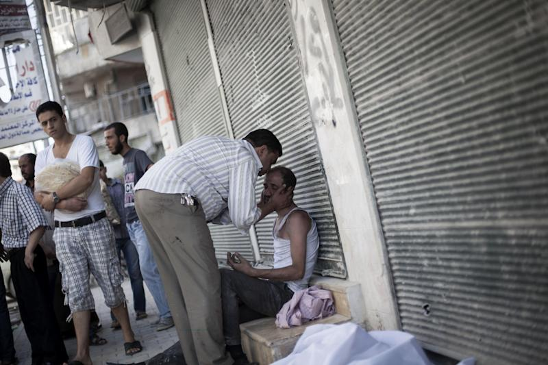 A Syrian man is comforted after the death of his brother, killed by a Syrian Army sniper, outside Dar El Shifa Hospital in Aleppo, Syria, Thursday, Sept. 27, 2012. (AP Photo/ Manu Brabo)
