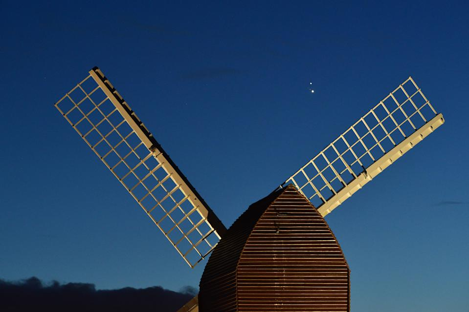 BRILL, ENGLAND - DECEMBER 20:  Jupiter and Saturn are seen coming together in the night sky, over the sails of Brill windmill, for what is known as the Great Conjunction, on December 20, 2020 in Brill, England. The planetary conjunction is easily visible in the evening sky and will culminate on the night of December 21. This is the closest the planets have appeared for nearly 800 years. (Photo by Jim Dyson/Getty Images)