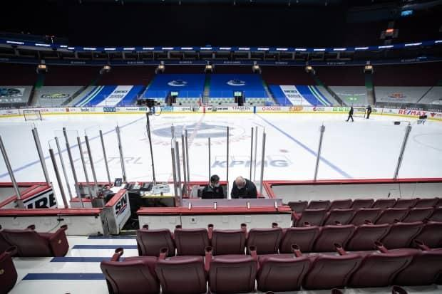 Off-ice officials pack up equipment after the Vancouver Canucks and Calgary Flames NHL hockey game was postponed due to a positive COVID-19 test result in Vancouver on Wednesday, March 31, 2021.