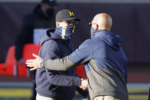 Michigan head coach Jim Harbaugh, left, greets Penn State head coach James Franklin after an NCAA college football game, Saturday, Nov. 28, 2020, in Ann Arbor, Mich. Penn State won 27-17. (AP Photo/Carlos Osorio)